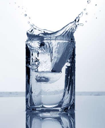 water splash: agua clara y el hielo en un vaso sobre fondo blanco y azul