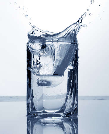 splash of water: clear water and ice in a glass on white and blue background Stock Photo