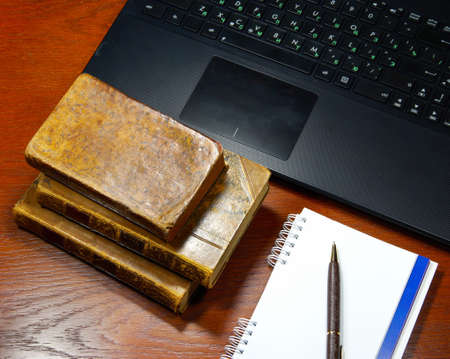 pad and pen: laptop, antique books and notebook on a wooden table Stock Photo