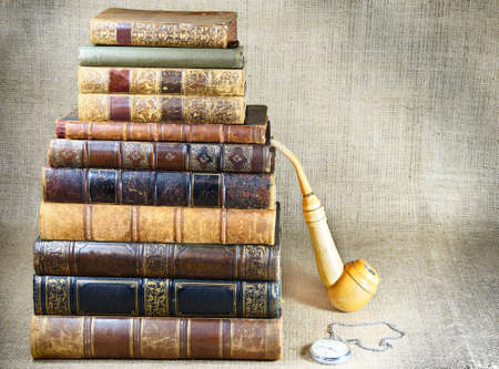 scientific literature: antiquarian books, tobacco pipe and the clock on the canvas background