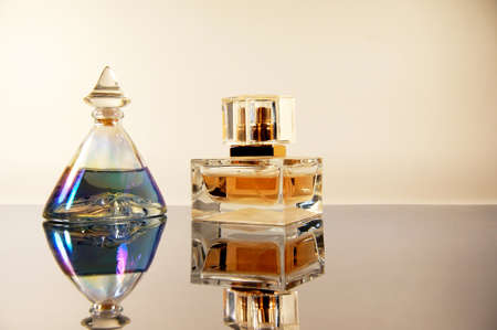 fascinate: two bottles of perfume on mirror surface