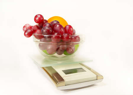 Scales with grapes, lime and orange isolated photo