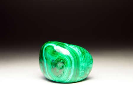 malachite: polished stone malachite on a light background Stock Photo