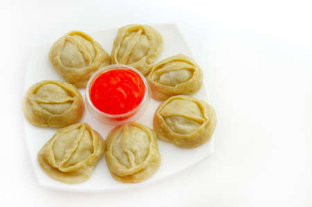 menue: manti and spicy sauce on a white plate