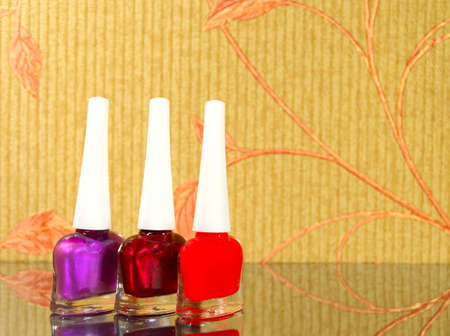 reddening: three bright vial of nail polish on the mirror surface