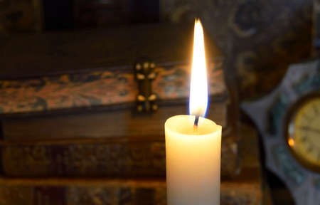 christmas concept: light candles and the vintage books behind