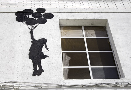 window graffiti: Girl with balloons flying over the wall, fantasy and imagination