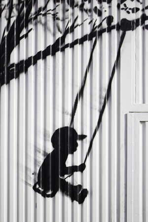 Child on swing drawn on door, silhouette and urban art photo