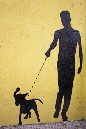 Man walking dog silhouette drawn on the wall, urban art photo