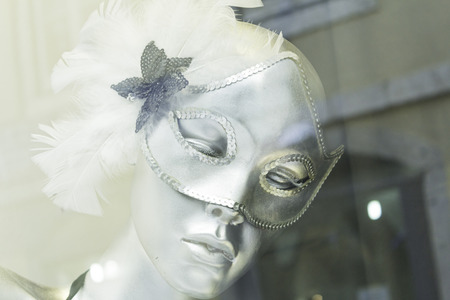 Mask in shop window mannequin in costume photo