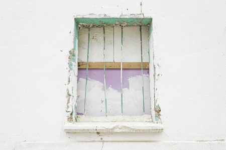 Barred in old broken house window, Construction photo