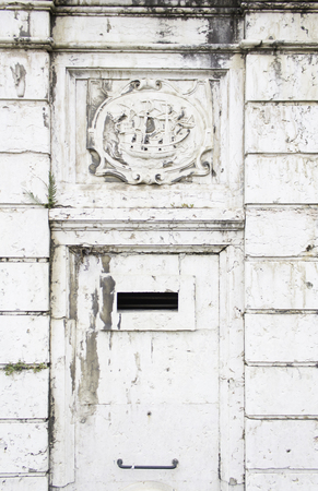 deteriorated: Historic building with ship on marble shield Stock Photo