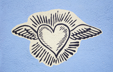 Heart with wings painted on city wall, symbol