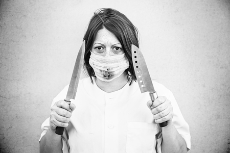 Nurse with knives and bloody mask, halloween photo