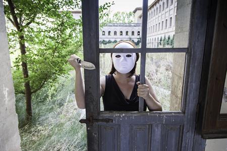 insane insanity: Murderer hiding in abandoned house door, halloween Stock Photo
