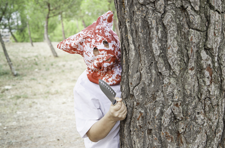 Murderer in forest with knife in park, halloween Stock Photo
