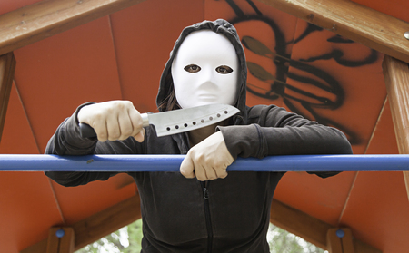 murderer: Murderer in playground with mask and knife, halloween Stock Photo