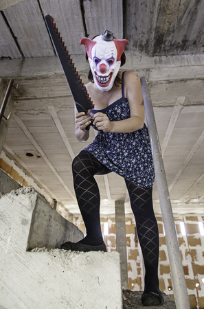 Crazy clown with saw, murderer and halloween