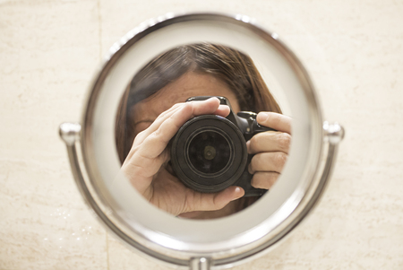 wor: Girl taking photo with camera in mirror work
