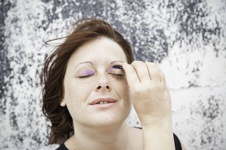 Young Girl Painting shade of purple eyes, beauty photo
