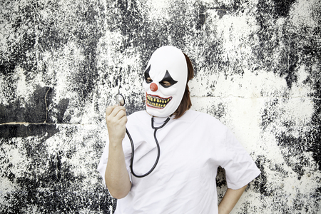 insanity: Clown doctor with stethoscope, medicine and fear Stock Photo