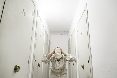 fear: Woman with bandaged storage white coat, fear Stock Photo