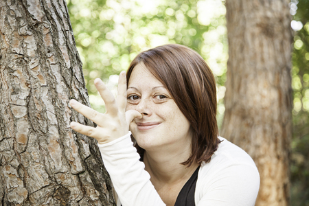 mockery: Girl behind tree mocking nature and people Stock Photo