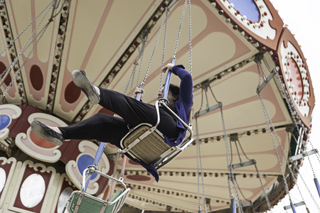 county fair: Woman on flying amusement park swings, fun Stock Photo