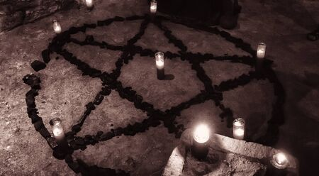 Pentacle demon with candles in celebration witchcraft, halloween and fear