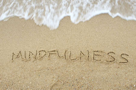 Mindfulness written on sand