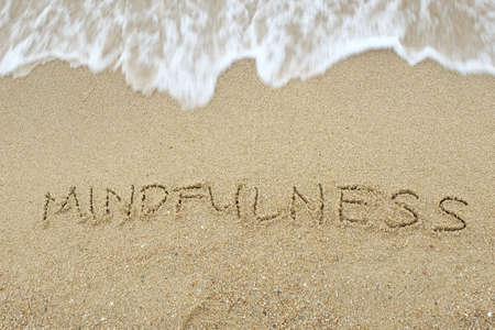 Mindfulness written on sand 版權商用圖片 - 84000734