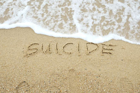 SUICIDE written on sand with wave approaching Stock Photo