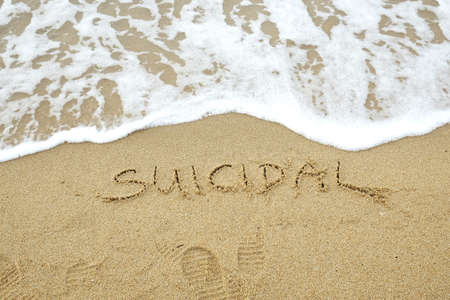 Suicidal written on sand with wave approaching Stock Photo
