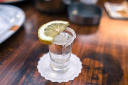 shot glass filled with tequila service with lemon and salt focused open air pub bar