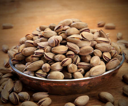 cracked pistachios in a bowl on wooden table