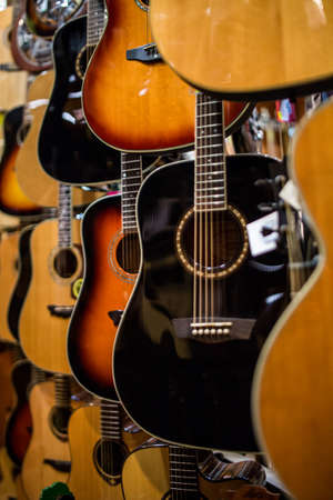 metal string acoustic guitars hanging on the walls of music store ready to perform