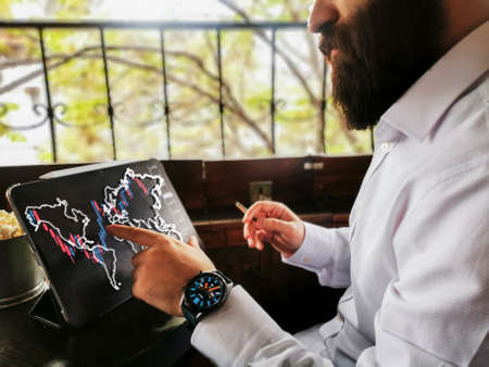 Bearded young businessman adult with smart watch using pro tablet touch screen to connect world and check the stock market forex and smoking 免版税图像