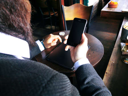 hipster businessman looking at his blank smart phone and pro tablet screens on the table at bar pub 免版税图像