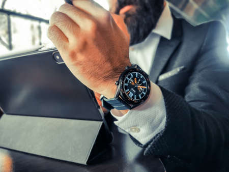 bearded adult rich businessman who has smart watch using his pro tablet and work remotely