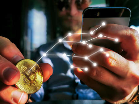 young adult male with sunglasses and watch using his smartphone and flipping bitcoin holographic network web on the table