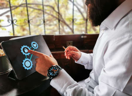 young adult with beard smart watch and cigar touching lock icon on his pro tablet 免版税图像