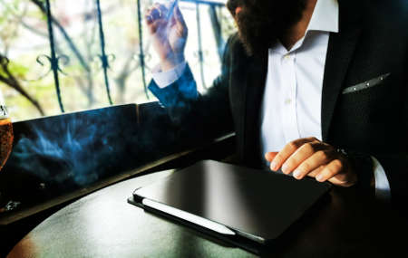 young adult bearded businessman with smart watch smoking cigar with blank pro tablet screen