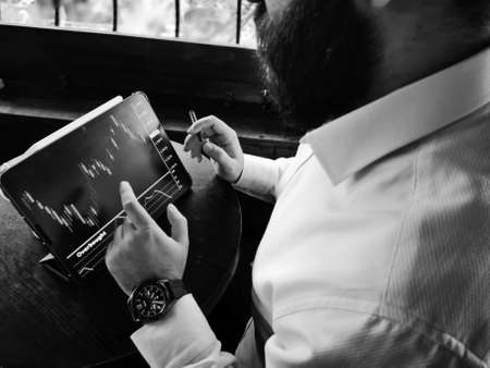 bearded adult rich businessman checking stock market for-ex on his pro tablet with smart watch black and white