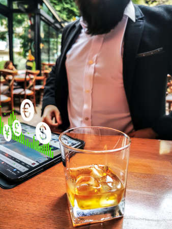 business man with beard using pro tablet and pencil interacting with tablet screen holographic economy for-ex currency icons floating euro us dollars yuan and gbp drinking whiskey in the cafe pub 免版税图像