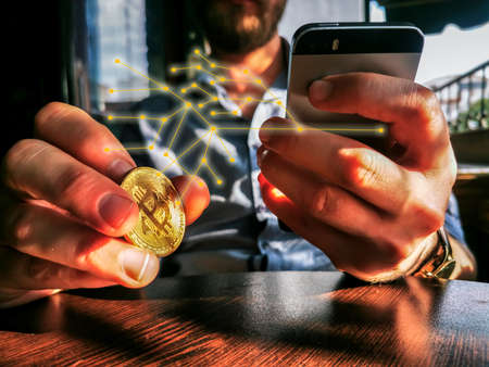 bitcoin holding rich male using his phone for remote exchange e-commerce e-business on the pub table 免版税图像