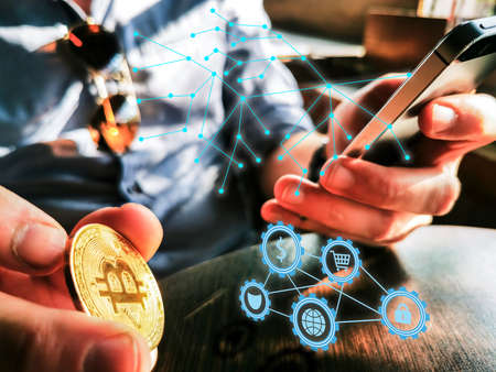 young adult male with sunglasses and watch using his smartphone and flipping gold bitcoin on the table holographic network web and e-commerce icons