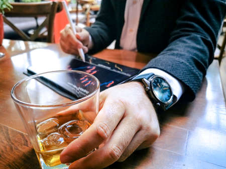 business man with beard who has smart watch using pro tablet and pencil interacting with tablet screen holographic economy icons drinking whiskey in the cafe pub 免版税图像