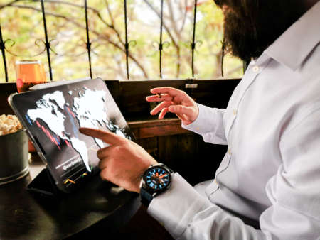 young adult with beard smart watch and cigar touching world map on his pro tablet