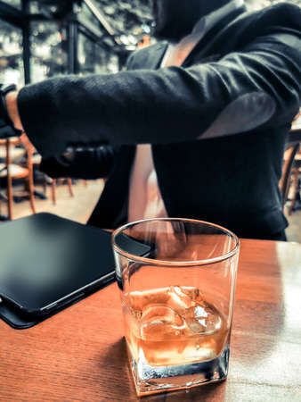 business man in cafe bar pub restaurant drinking whiskey with his blank screen tablet pro