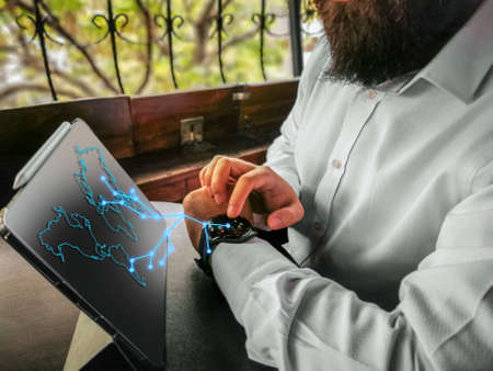 bearded adult rich businessman touching economy touching his smart watch and connecting to his pro tablet and internet world map holographic 免版税图像